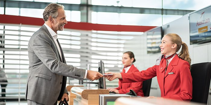 Businessman receives his boarding card at the check-in counter