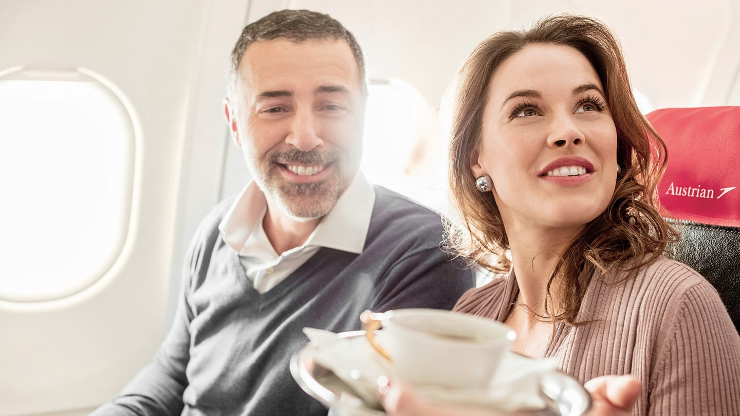 A man and a woman are served coffee in business class