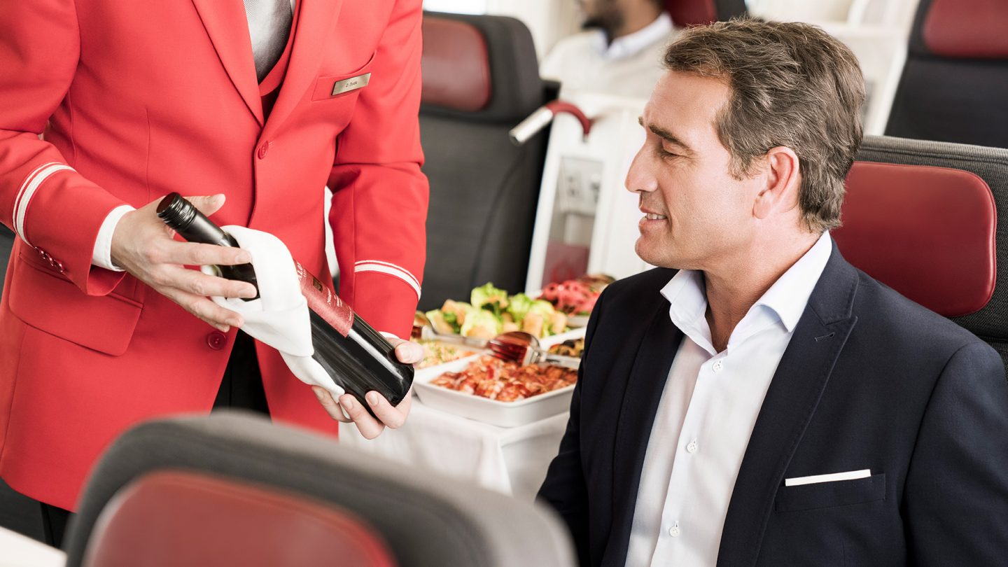 A flight attendant presents a bottle of wine to the passenger