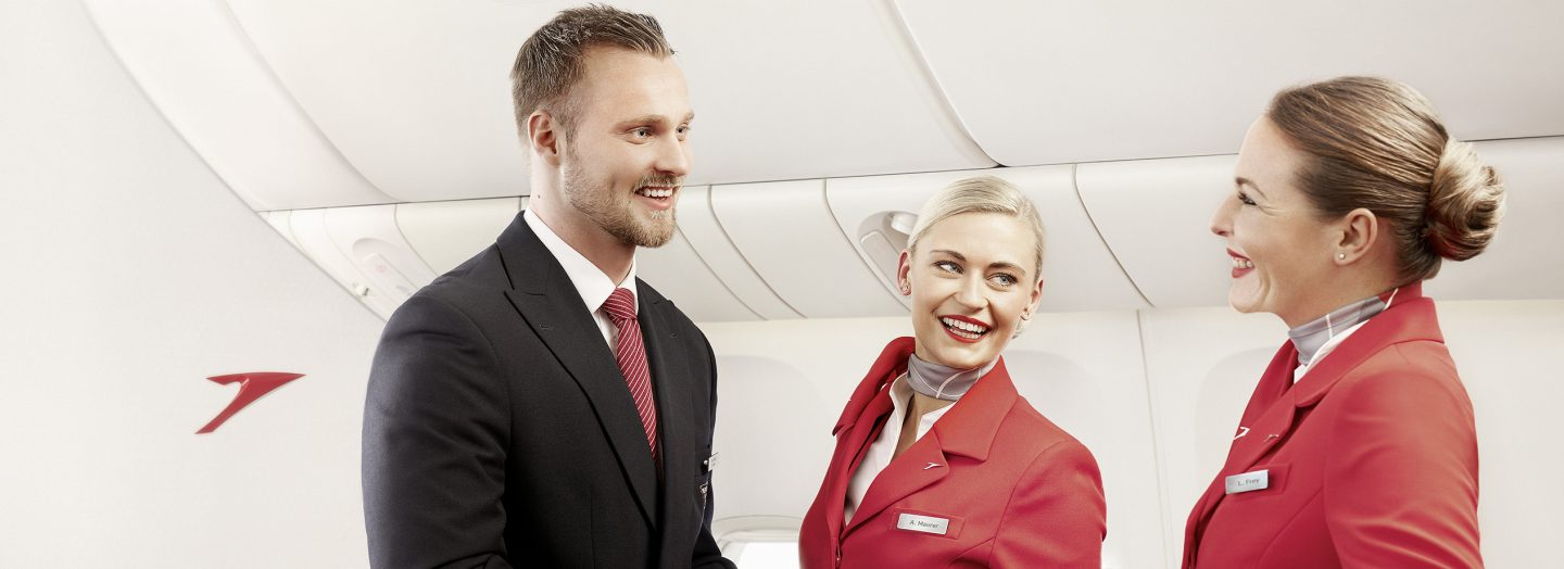 Two flight attendants talking to their colleague