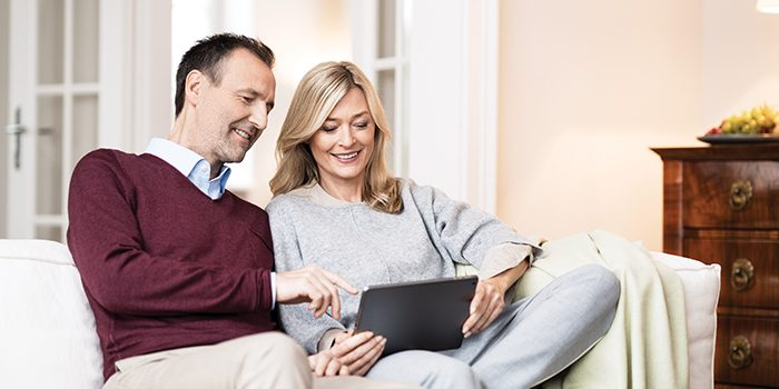 A couple is sitting on the sofa with a tablet