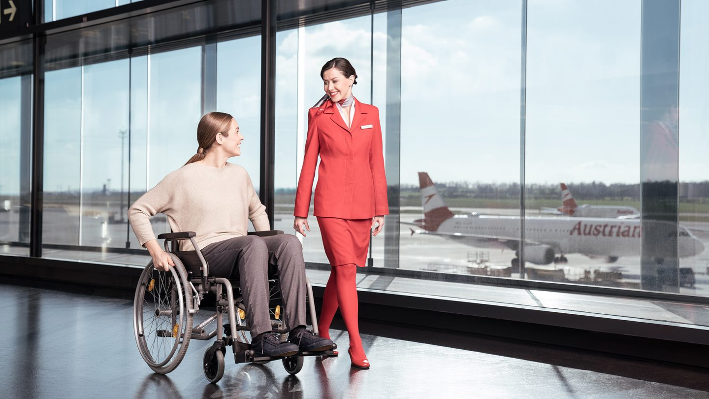 Woman in a wheelchair with Austrian flight attendant at the airport